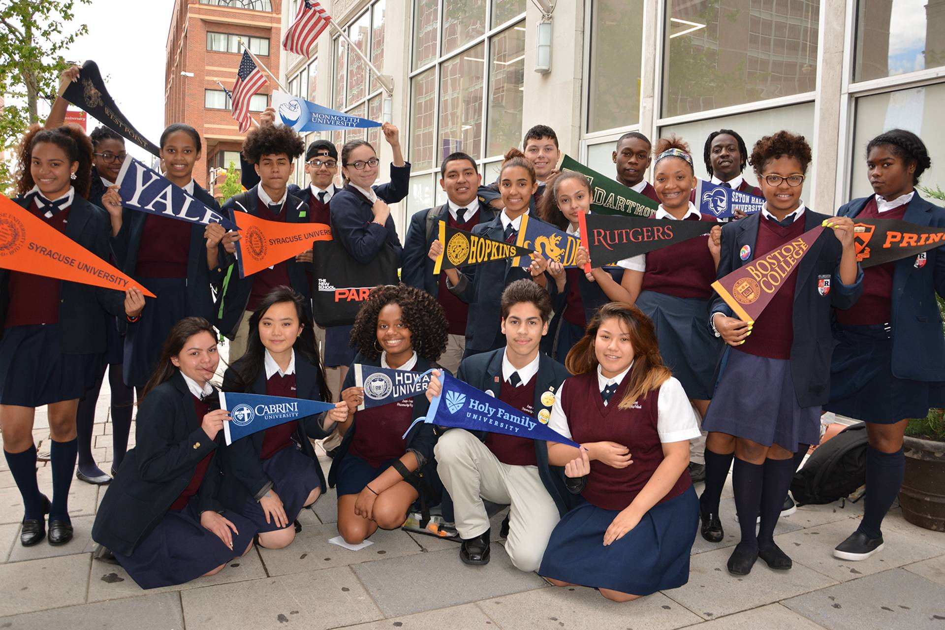 LEAP Academy graduates holding flags of the various instituations they were accepted to